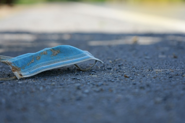 La maschera chirurgica dopo l'uso è caduta sulla strada pericolosa e sporca sulla strada