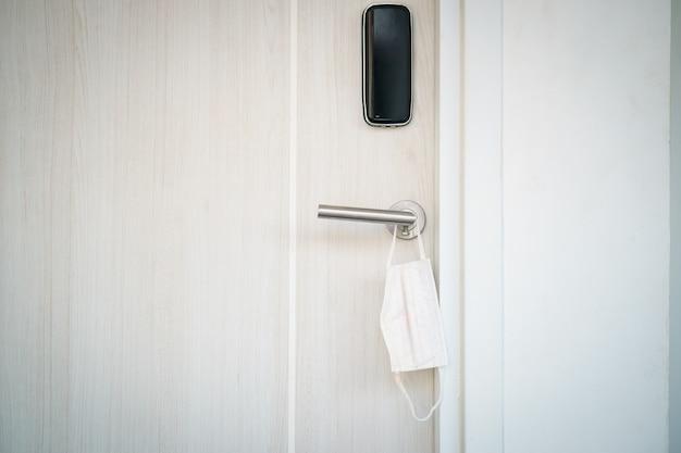 Maschera chirurgica appesa alla maniglia della porta. ricorda di indossare prima di uscire.