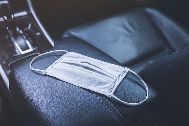 Maschera chirurgica posizionata sulla scatola del bracciolo in un'auto