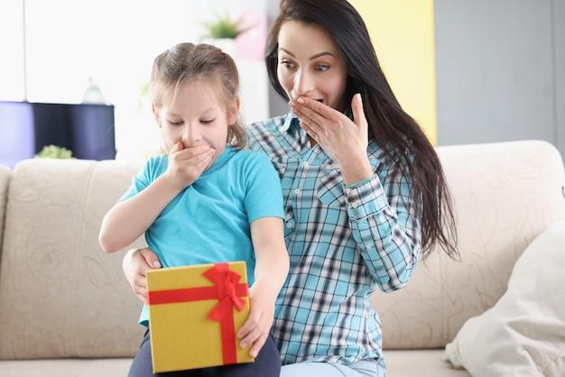Sorpresa e ammirazione, mamma e figlia guardano in una luminosa confezione regalo