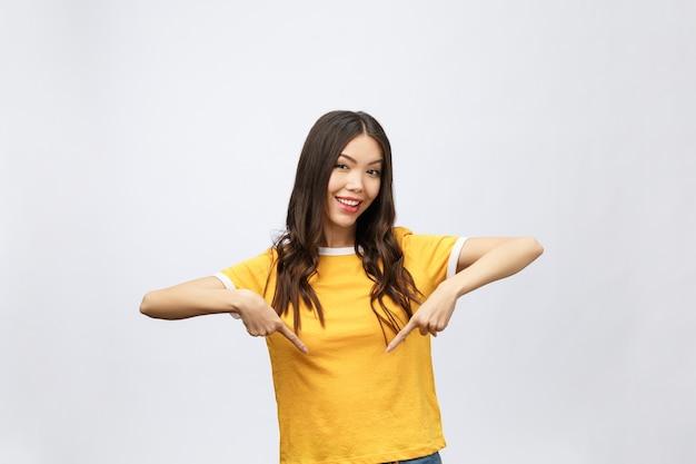 Sorpresa donna asiatica con il dito puntato verso l'alto isolare su bianco