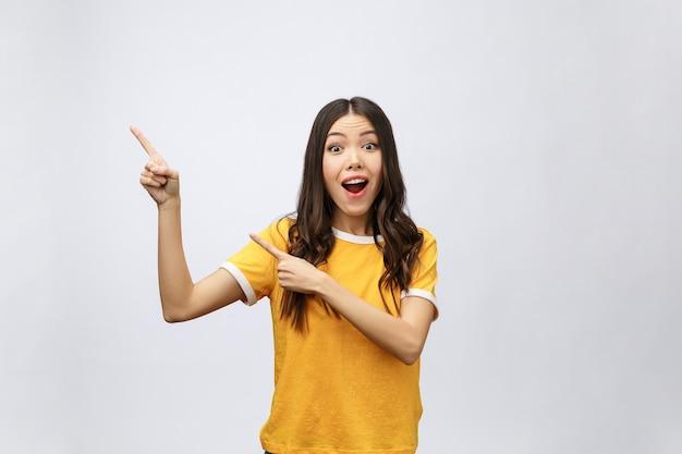 La donna asiatica di sorpresa con il dito punta verso l'alto isolare su bianco