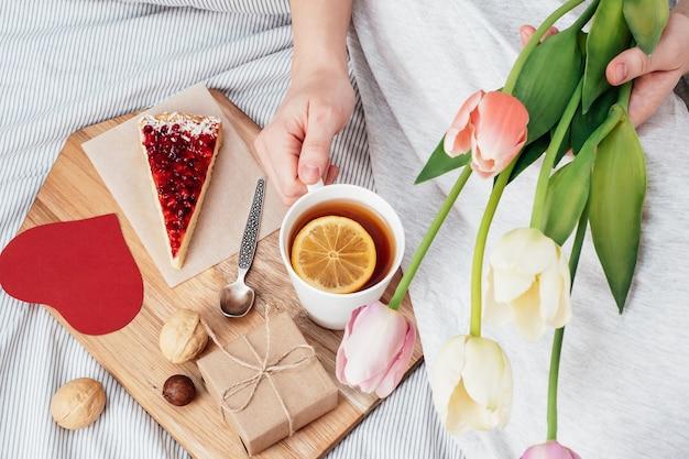 Sorpresa a letto. colazione, fiori e un regalo per una ragazza a san valentino. congratulazioni per il 14 febbraio.