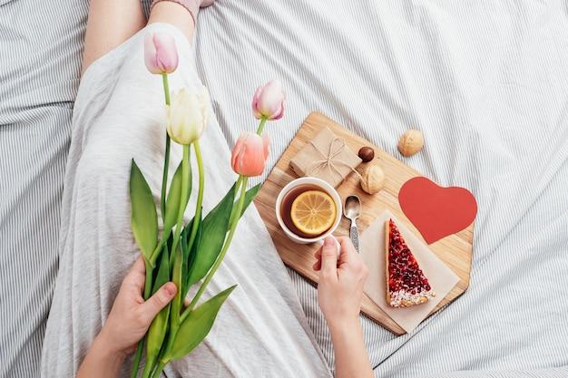 Sorpresa a letto. colazione, fiori e un regalo per una ragazza a san valentino. congratulazioni per il 14 febbraio. Foto Premium