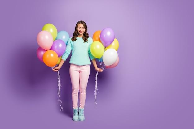 Sorpresa! ritratto a grandezza naturale di bella signora porta molti palloncini colorati amici festa evento indossare maglione menta sfocato rosa pastello pantaloni stivali.