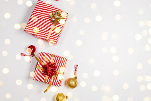 Scatole regalo a sorpresa avvolte in carta artigianale con fiocco dorato, abete e palline rosse dorate