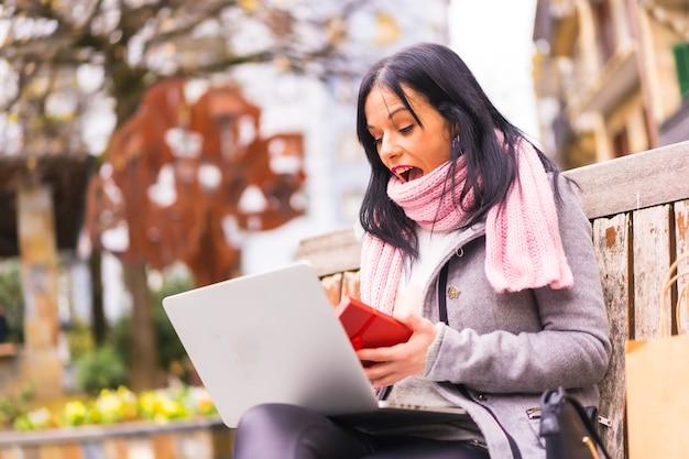 Regalo a sorpresa, ragazza bruna caucasica che apre il regalo del fidanzato in una videochiamata con il computer, separato dalla distanza