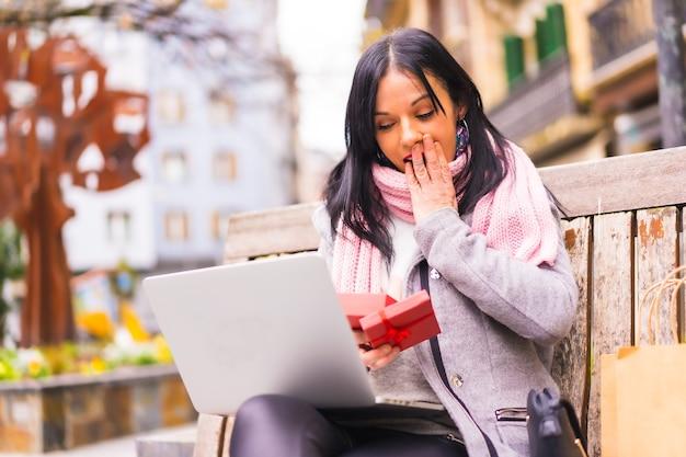 Regalo a sorpresa, ragazza molto eccitata che apre il regalo del fidanzato in una videochiamata con il computer, separato dalla distanza