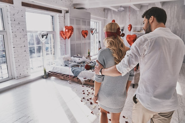 Sorpresa per lei. vista posteriore della giovane donna che cammina con gli occhi bendati attraverso la camera da letto con il suo ragazzo