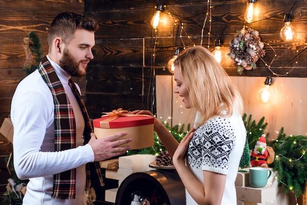 Sorpresa per la dolce metà. buon natale e felice anno nuovo. regali di natale. uomo bello con sorpresa di scatola regalo per la ragazza. l'uomo pantaloni a vita bassa dà un regalo alle decorazioni natalizie della ragazza.
