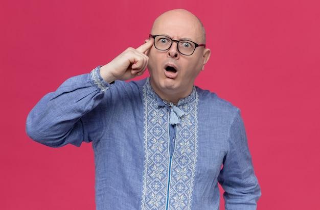 Uomo slavo adulto sorpreso in camicia blu che indossa occhiali ottici mettendo il dito sulla tempia e