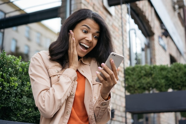Sorpresa donna afro-americana utilizzando il telefono cellulare, guardando lo schermo digitale, ha vinto la lotteria in linea, celebrazione del successo