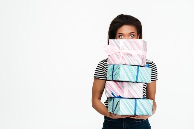 Donna africana sorpresa che si nasconde dietro il mucchio delle scatole attuali