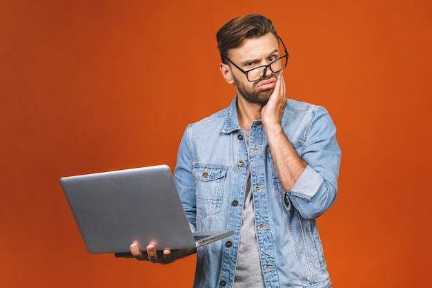 Sorpreso stupito giovane uomo d'affari in piedi casual e tenendo il portatile isolato su uno sfondo arancione