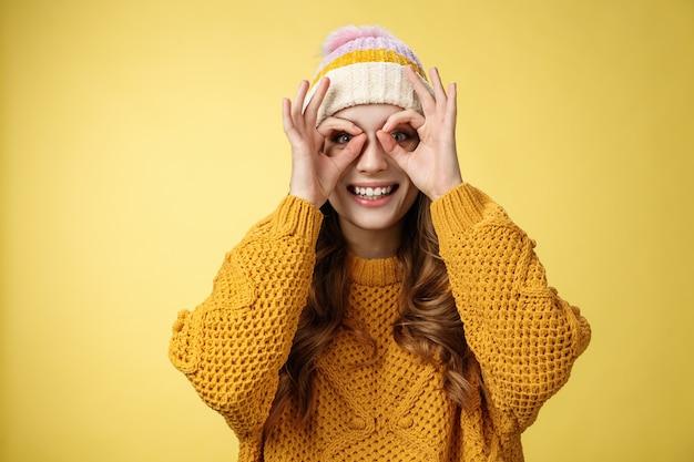 Sorpreso divertito interessato attraente giovane donna europea che indossa un cappello di velluto a coste maglione lavorato a maglia allarga gli occhi curioso mostra occhiali binoculari fatti dita, sorridendo stupito, sfondo giallo