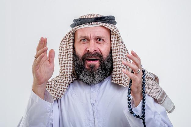 Uomo arabo sorpreso in posa su sfondo bianco.
