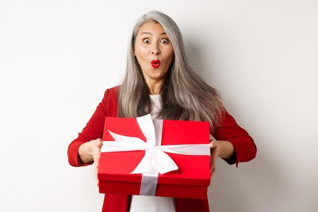 Donna senior asiatica sorpresa che riceve presente il giorno della madre, che tiene la scatola rossa con il regalo e che guarda stupito alla macchina fotografica, fondo bianco.