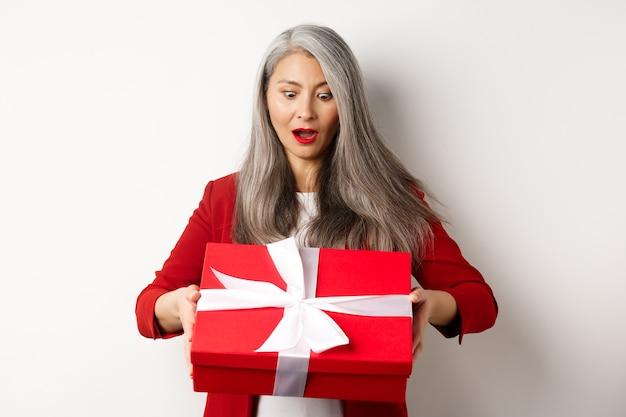 Donna senior asiatica sorpresa che riceve presente il giorno della madre, tenendo la scatola rossa con il regalo e guardando stupito, sfondo bianco.