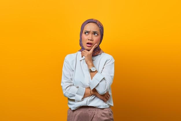 Donna asiatica sorpresa che guarda in alto e si tocca la guancia con le dita su sfondo giallo