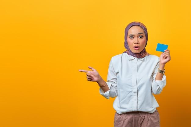 Donna asiatica sorpresa che indica uno spazio vuoto e tiene in mano una carta bianca su sfondo giallo