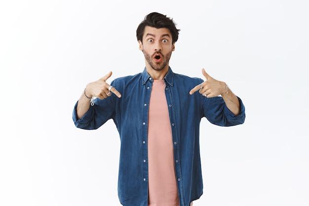 Uomo barbuto caucasico di bell'aspetto sorpreso e stupito in t-shirt, camicia, che punta verso il basso e sorride stupito, mostrando notizie entusiasmanti, consiglia un prodotto indispensabile, in piedi muro bianco