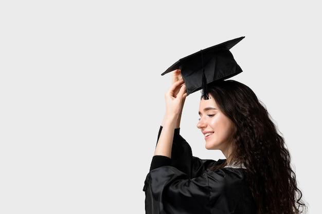 Ragazza di scapolo sorpresa in veste e berretto di laurea. apprendimento a distanza online. studia a casa. laurea dal college.
