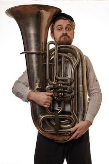Uomo barba sorpreso con bretelle e cappuccio che tiene il tubo
