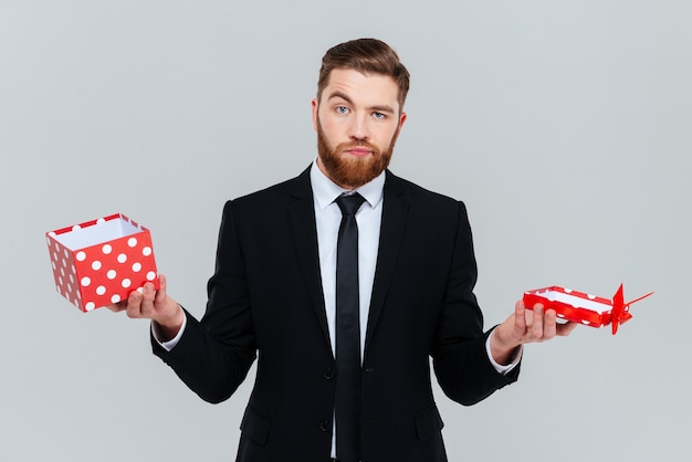 Uomo d'affari barbuto sorpreso in vestito che tiene regalo aperto vuoto nelle mani. sfondo grigio isolato