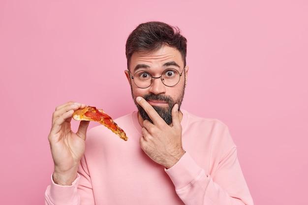 L'uomo barbuto sorpreso tiene una fetta di pizza mangia il fast food ha uno spuntino gustoso per il buon umore indossa occhiali rotondi maglione casual a maniche lunghe