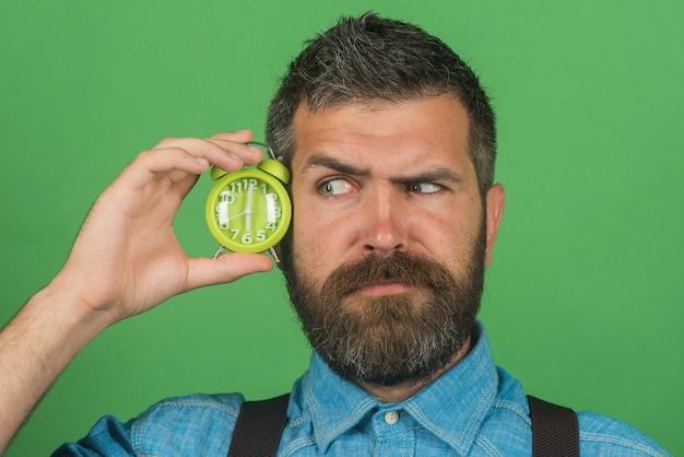 L'uomo barbuto sorpreso con l'acconciatura alla moda in camicia del denim tiene il macho attraente della sveglia con