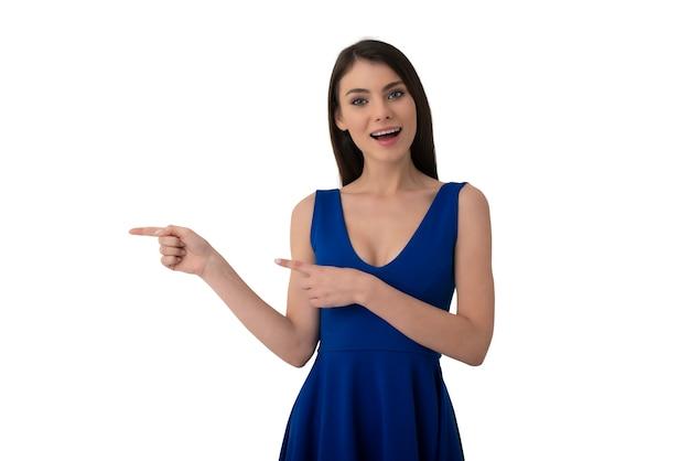 La bella ragazza sorpresa indica uno spazio vuoto per il tuo testo. isolato su sfondo bianco