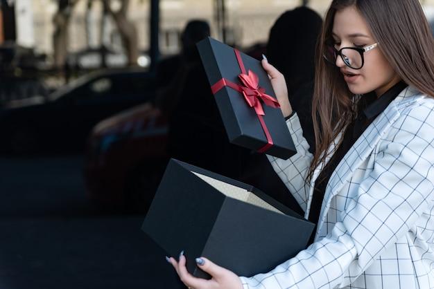 La bella donna sorpresa ha aperto il contenitore di regalo. felice giovane donna con regalo sulla strada. la ragazza ha ricevuto un regalo e l'ha aperto.