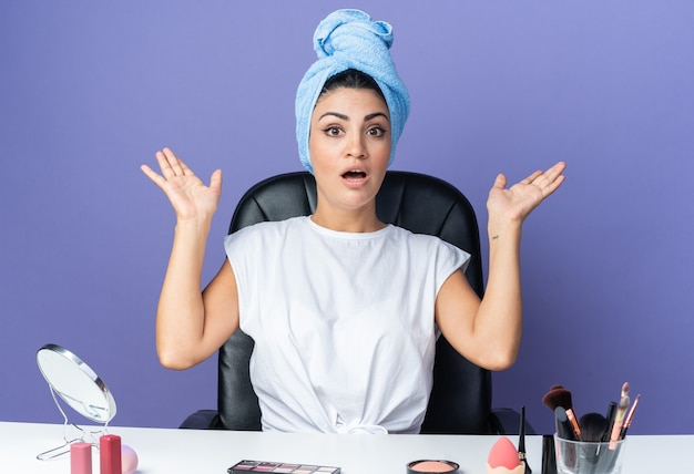 La bella donna sorpresa si siede al tavolo con gli strumenti per il trucco avvolti i capelli in un asciugamano che allarga le mani