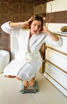 Bella donna sorpresa in piedi sulla bilancia da bagno infelice e preoccupata per il suo peso. concetto di sovrappeso e dieta.