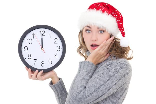 Bella donna sorpresa in abiti invernali e cappello da babbo natale che tiene l'orologio isolato su sfondo bianco