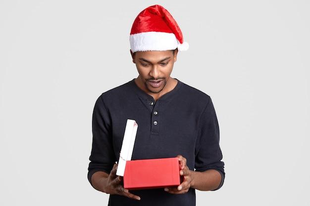 Il maschio nero sorpreso osserva con sorpresa il contenitore di regalo, vede un regalo costoso, porta una scatola, indossa un cappello di babbo natale e un maglione casual