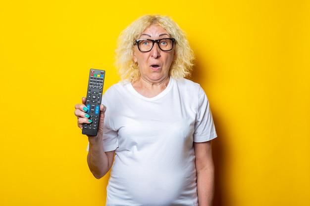 Donna anziana bionda sorpresa con gli occhiali che tengono telecomando