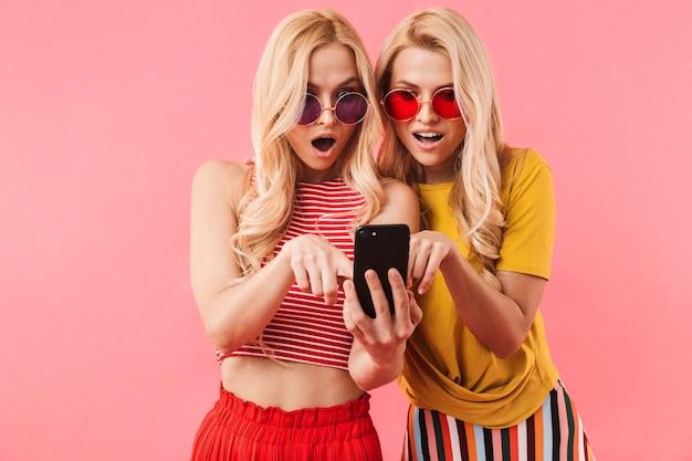 Gemelli biondi sorpresi in occhiali da sole che utilizzano smartphone con la bocca aperta sul muro rosa