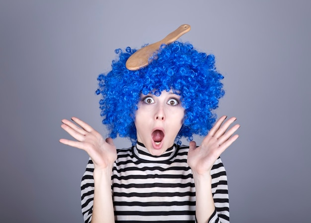 Ragazza blu sorpresa dei capelli con il pettine bloccato.