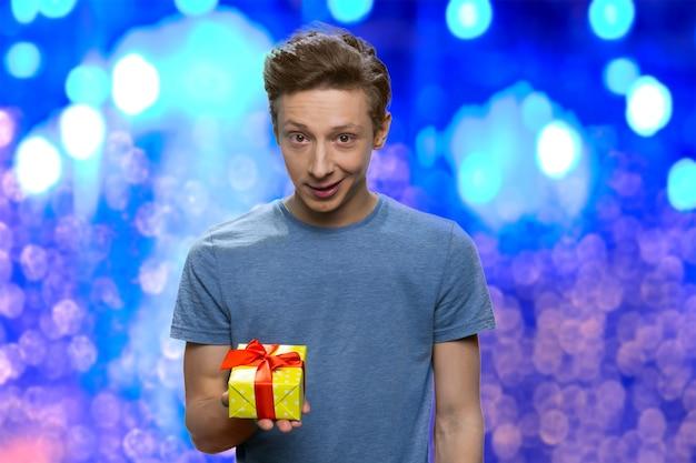 Il ragazzo sorpreso tiene in mano una piccola scatola regalo gialla