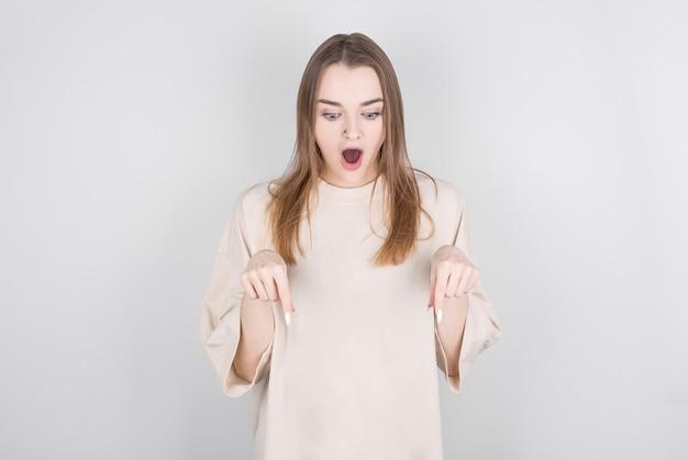 La donna castana sorpresa indica il pavimento, ha un'espressione facciale scioccata