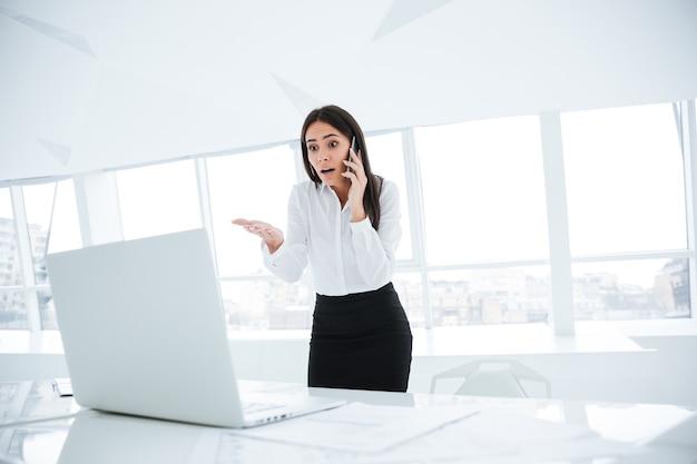 Donna d'affari sorpresa in piedi vicino al tavolo, guardando il laptop e parlando al telefono in ufficio