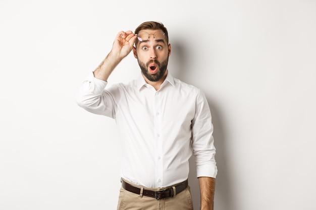 Uomo d'affari sorpreso che si toglie gli occhiali, guarda con stupore la telecamera, in piedi su sfondo bianco