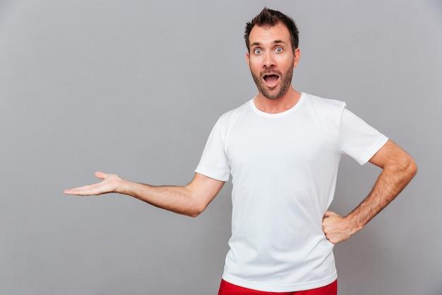 Uomo casuale sorpreso che tiene copyspace su un palmo su sfondo grigio