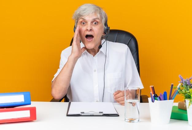 Operatore di call center femminile caucasico sorpreso sulle cuffie seduto alla scrivania con strumenti da ufficio tenendo la mano vicino alla bocca