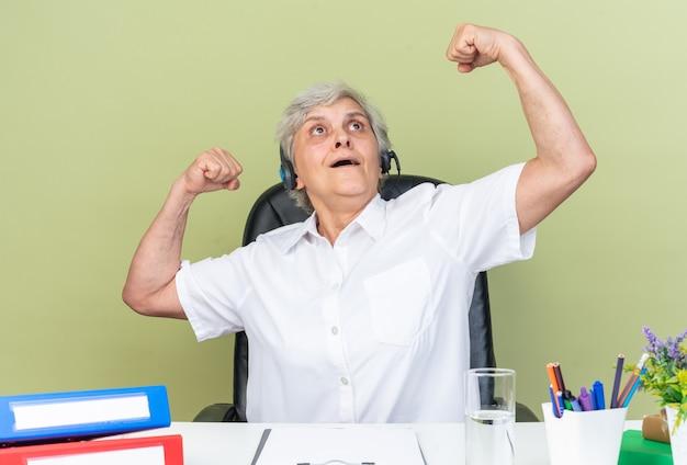Operatore di call center femminile caucasico sorpreso sulle cuffie seduto alla scrivania con strumenti da ufficio tendendo i suoi bicipiti guardando in alto isolato sulla parete verde