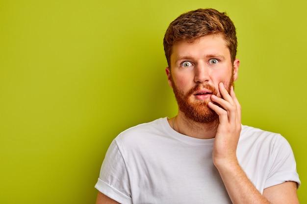 Maschio caucasico sorpreso che guarda l'obbiettivo in una perdita, ragazzo emotivo con la barba stare con le mani sul viso, spaventato da qualcosa, isolato sopra lo spazio verde