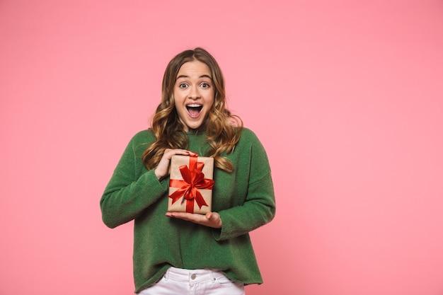 Donna bionda allegra sorpresa che indossa un maglione verde che tiene in mano una confezione regalo e si rallegra mentre guarda la parte anteriore sul muro rosa