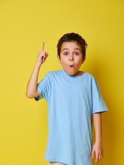 Ragazzo bambino sorpreso, puntando il dito indice su uno sfondo giallo con spazio di copia.