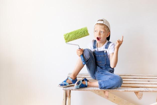 Un bambino sorpreso builder si siede su una scala di costruzione in un appartamento e un rullo nelle sue mani